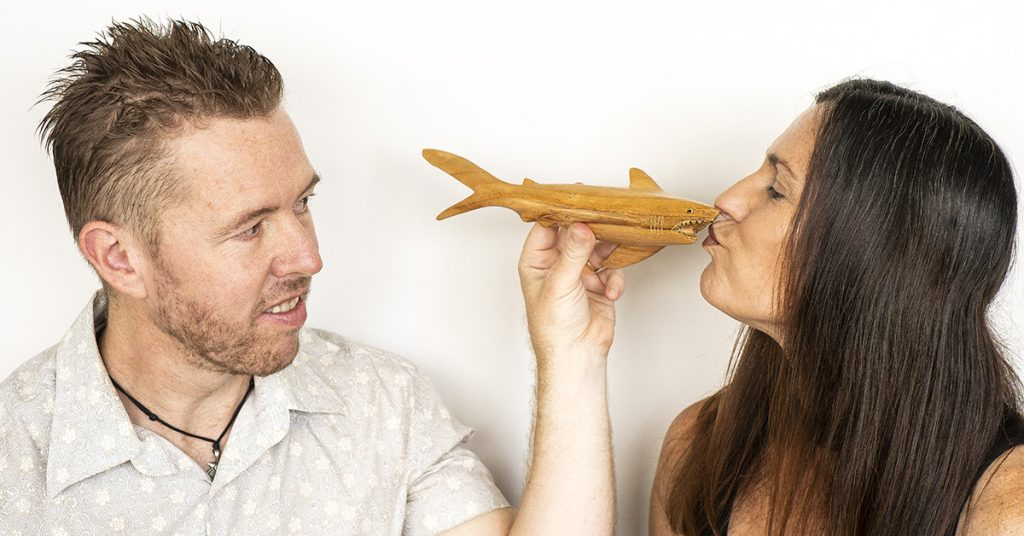 Tim and Anita Horan play with a wooden shark.