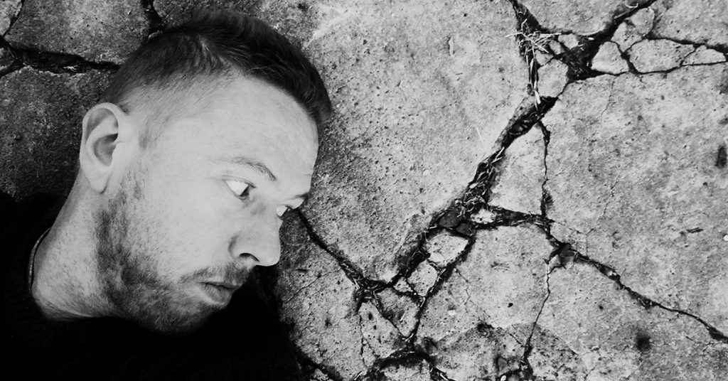 Photo of Tim Horan contemplating cracks in a slab of concrete.
