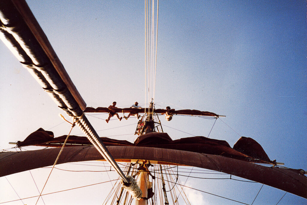 Crew members go aloft to unfurl The Eye of the Wind's sails.