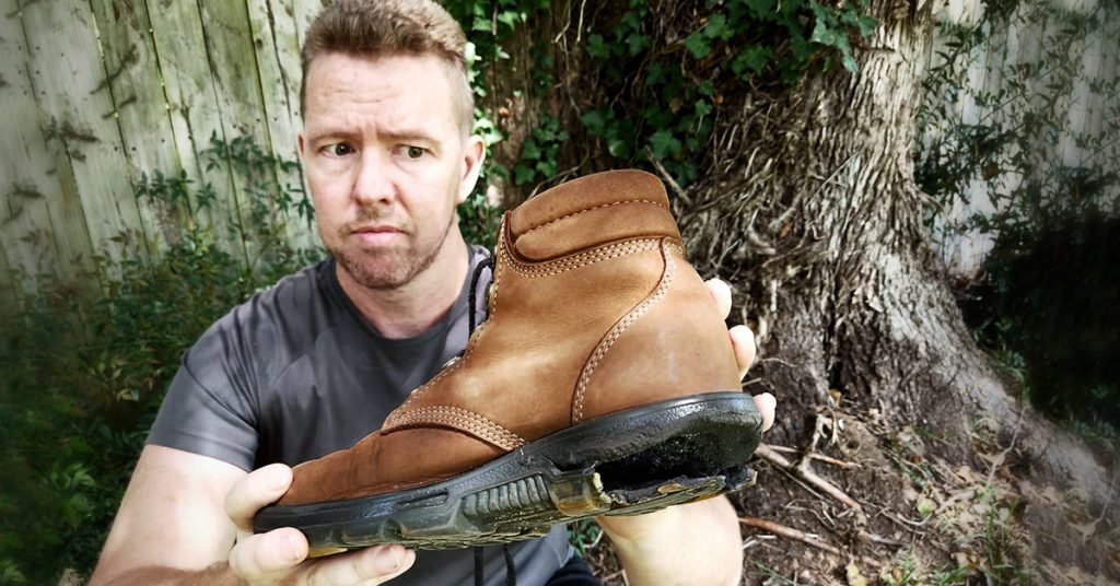 Tim Horan holds one of his hiking boots with a ruined heel.