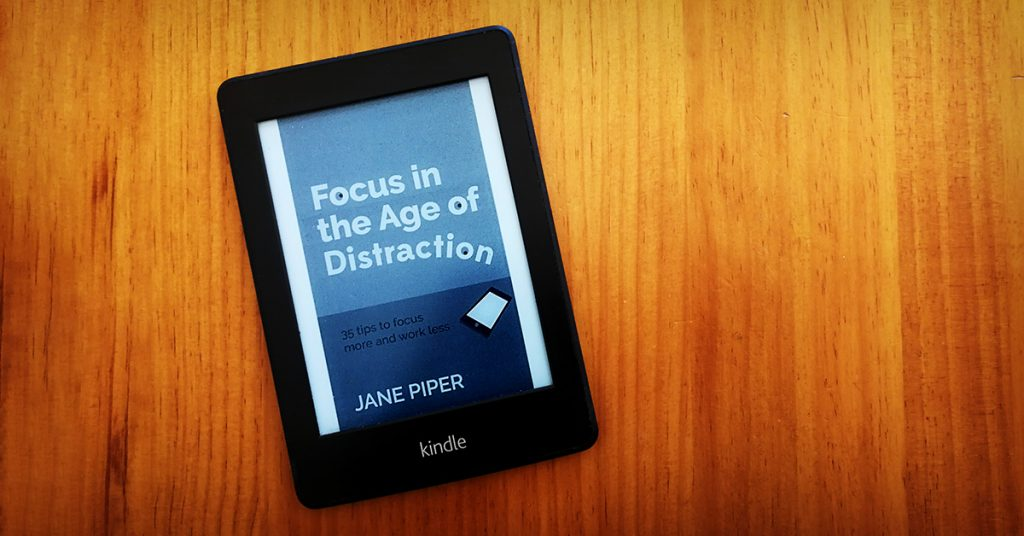 Tim Horan's kindle e-reader with the cover of 'Focus in the Age of Distraction' by Jane Piper on the display.