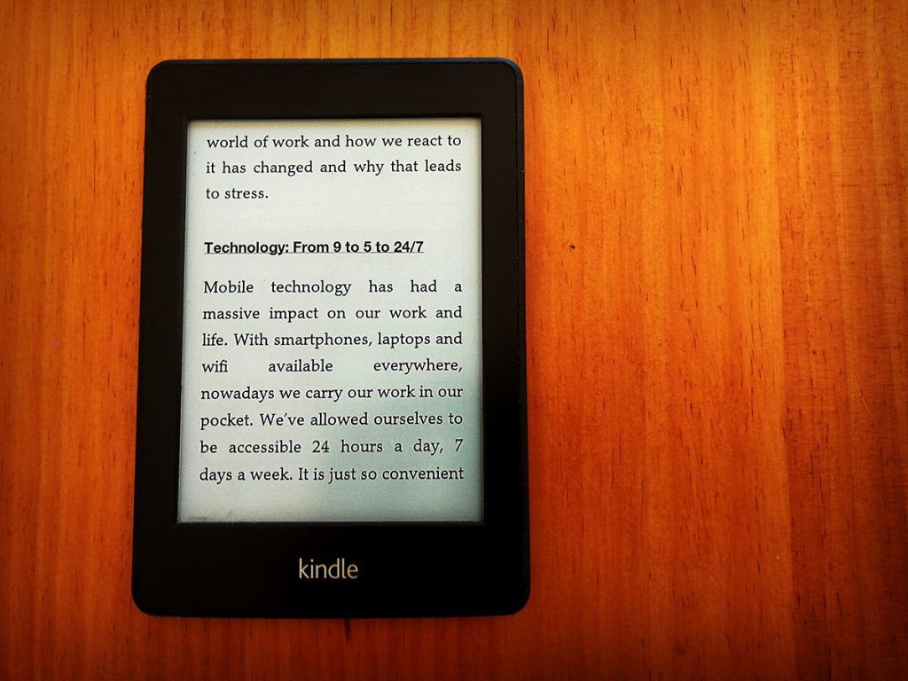 """Tim Horan's kindle with the subheading """"Technology: From 9 to 5 to 24/7"""" from Jane Power's book 'Focus in the Age of Distraction' on the screen."""