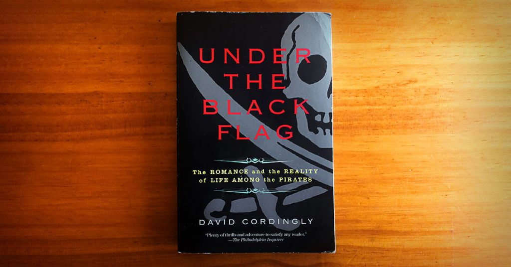 Tim Horan's paperback copy of 'Under the Black Flag' by David Cordingly on his timber dining table.