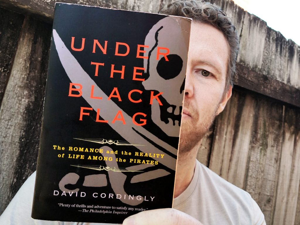 Photo of Tim Horan holding his copy of 'Under the Black Flag: The Romance and the Reality of Life Among the Pirates' by David Cordingly.